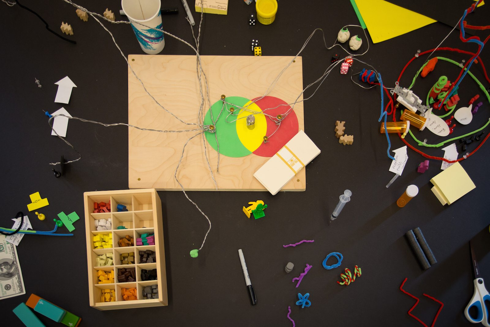 Aerial shot of a table in Georgetown's EthicsLab scattered with wood, felt, springs, pipe cleaners, markers, and other modeling materials